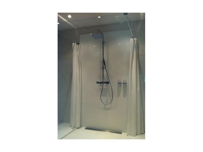 Une cabine de douche avec paroi de verre et deux rideaux de douche en lin blanc